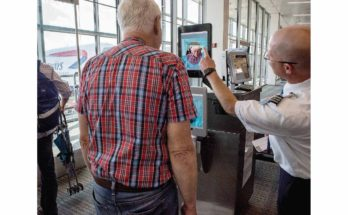 A Transportation Security Administration (TSA) screener uses a biometric facial recognition scanner on a traveler at Washington Dulles International Airport.