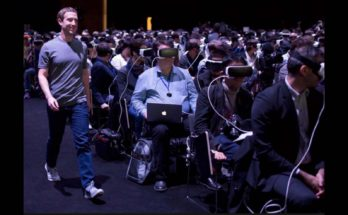 Mark Zuckerberg walks down aisle of theater full of people wearing Oculus augmented reality headsets. (It's a new wilderness)