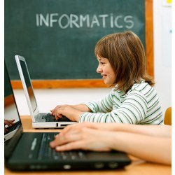 """Young girl at keyboard. """"Informatics"""" written on chalk board in background."""