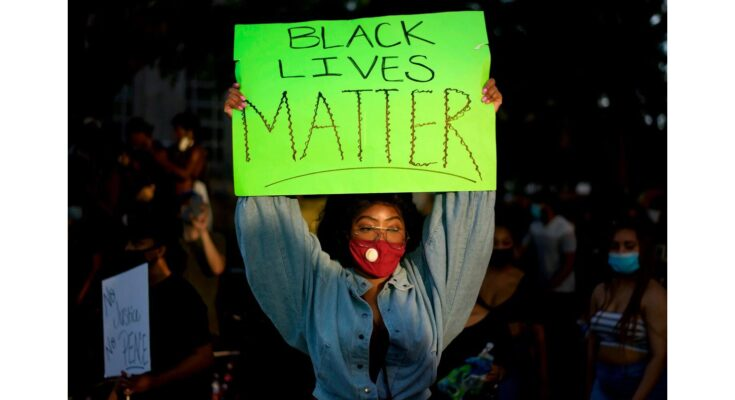 a protestor holding up a sign that reads Black Lives Matter - Photograph: MARK FELIX/Getty Images