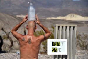 Steve Krofchik of Las Vegas keeps cool with a bottle of ice on his head as the thermometer reads 130 degrees (54.4 Celsius) at the Furnace Creek Visitors Center in Death Valley Monday. (David Becker/Reuters)