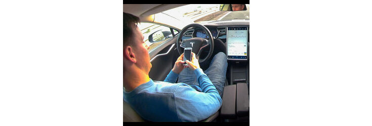 man in driver's seat of autonomous vehicle looks at cellphone - Credit: Shutterstock.com