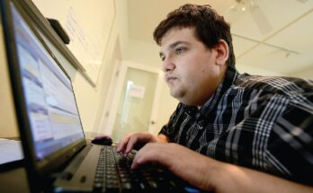 Figure. Analyst Corey Weiss, who was diagnosed with autism as a young boy, working at Mindspark. - Photo by Frederic J. Brown / AFP via Getty Images