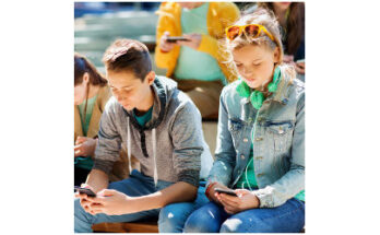 young male and female looking at smartphones - Credit: Syda Productions