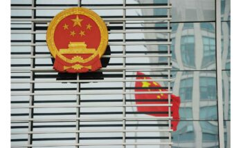 Chinese emblem on a building with a reflection of the Chinese flag - Photograph: PETER PARKS/Getty Images